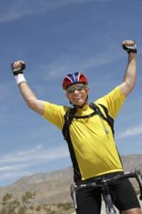 Senior Man Riding Bicycle And Cheering