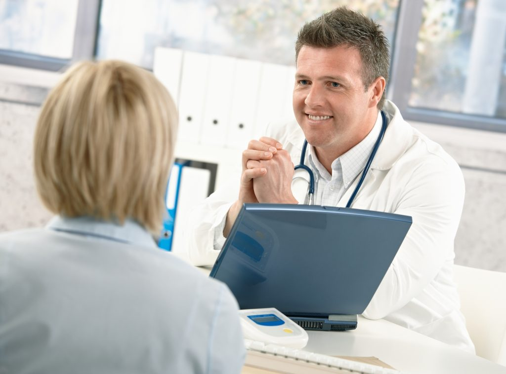 bigstock-Smiling-doctor-talking-to-pati-13111280-1024x758