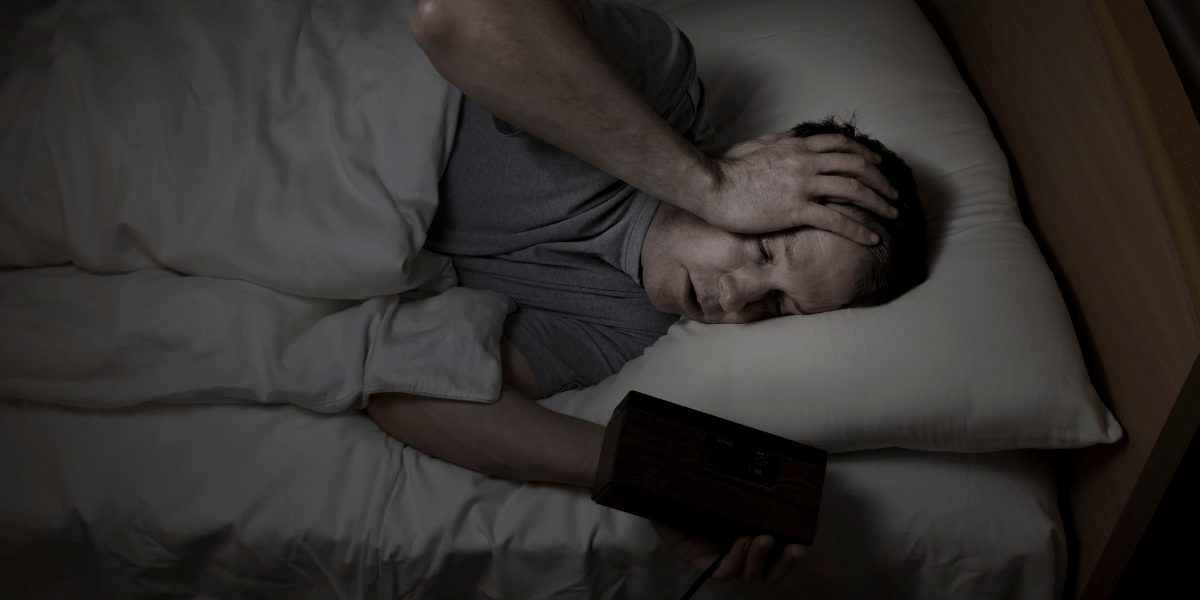 man awake in bed looking at alarm clock