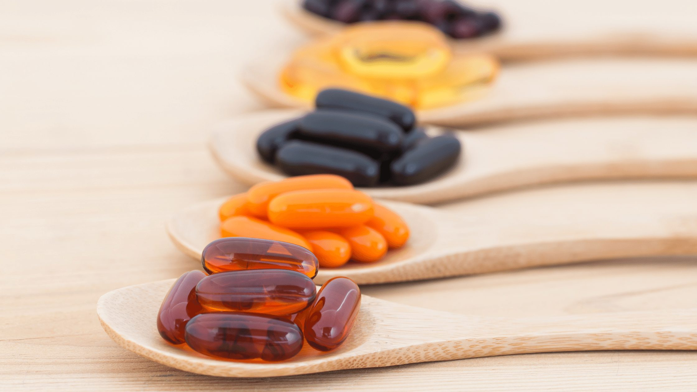 Multiple supplement pills organized on seperate wooden spoons